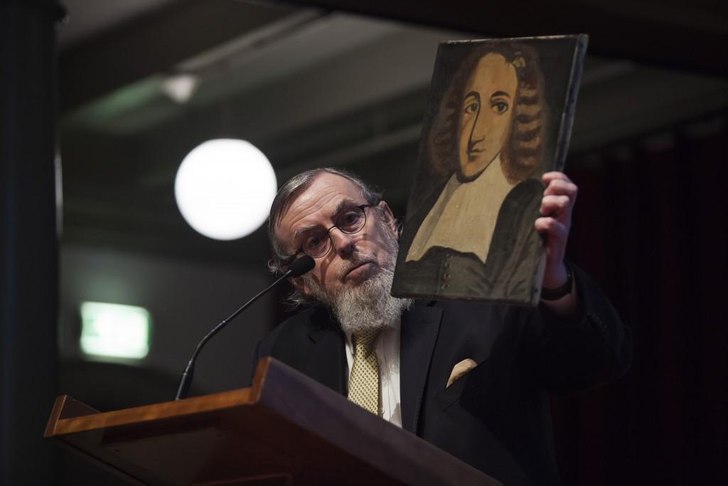 Rabbijn Nathan Lopes Cardozo in De Rode Hoed, met een portret van Baruch Spinoza. Foto: Claudia Kamergorodski